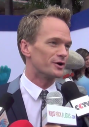 A man with dark blonde hair speaks into microphones away from the camera