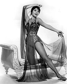 Dancer posing expressively in an ornate leotard and sheer fabric costume, one knee resting on an upholstered bench