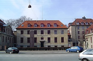 A block-shaped beige building with a sloped, red tiled roof