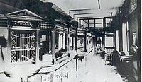 A black-and-white photograph of a bank lobby, with barred teller's windows at a counter on the left and windows and other furniture on the right. A partition is visible in the rear.