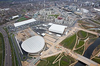East Village, London - View looking towards the Olympic and Paralympic Village, April 2012. In the foreground is the London Velopark, followed by the Basketball Arena and then the Village. To the top right is the London Aquatics Centre, to the right of which (out of shot) is the Olympic Stadium.