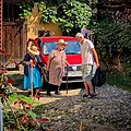 People chatting in front of a car in a courtyard in Transylvania, Romania.jpg
