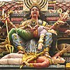 An eight-armed seated woman dressed in a sari, holding a child and various weapons, ripping the womb of a woman, lying on her lap, while trampling a man