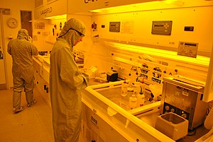 London Centre for Nanotechnology - Scientists in the photolithography laboratory in the London Centre for Nanotechnology cleanroom. The room is lit with orange lighting to avoid damage to the photoresist which could occur if there were ambient light at short wavelengths.