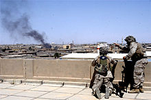 Two Marines on a rooftop observe billowing smoke from an Iraqi city.