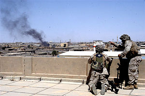 1st Battalion, 5th Marines - Marines with A/1/5 peer over a building top to fix enemy targets in Al Fallujah, Iraq 7 April 2004.
