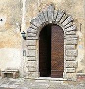 Porta secondaria sulla facciata della Chiesa di Santa Maria a Montepulciano.jpg