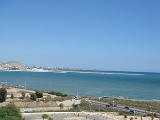 Port of Alicante - Panoramic view of Alicante Port's new extension, seen from the road entering the city from the airport. The (blue) terminal to the left of the ferry is 12 m high, the maximum height permitted. The Port has requested planning permission from the Ayuntamiento for 17 cement silos between 26 m and 55 m high on the outer quay to the right of the ferry.