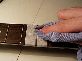 Guitar technician - Cleaning the frets of an electric guitar is part of the regular maintenance for this instrument