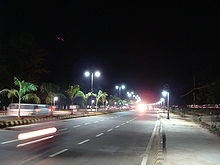 A wide road with lane markings, beautified median and decorative street lights