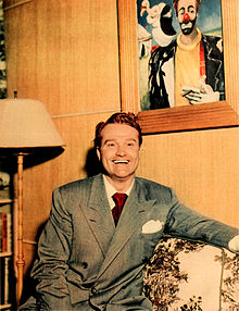 Skelton at home with one of his clown paintings, 1948