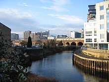 The canalised River Aire flows from the Dark Arches under Leeds's main railway station towards the bottom of the picture. To the left of the river is the lock which links the river with the Leeds and Liverpool Canal. To the right is a riverside walk beneath modern buildings, and in the distance, beyond the railway viaduct and station, are more high-rise modern buildings located on the west side of the city centre.