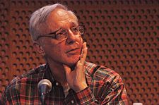 A man wearing a plaid-red shirt speaks into a microphone.