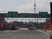 A split in a multi-lane freeway under construction with three green overhead signs. The left sign reads west Route 139 to U.S. Route 1 and 9 Interstate 280 Pulaski Skyway with two downward arrows, the middle sign reads Kennedy Boulevard Jersey City with two downward arrows, and the right sign reads New Jersey Turnpike Interstate 78 to Interstate 95 with two arrows pointing to the upper right.