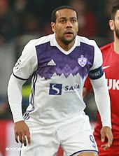 An Afro-Brazilian man in a white-purple football kit.