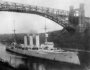A large ship with three smokestacks passes under a tall arch bridge