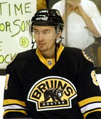 An ice hockey player standing, facing towards the camera. He is wearing a black helmet and a black, yellow and white uniform.