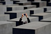 Tourist taking a picture at the Berlin Holocaust memorial