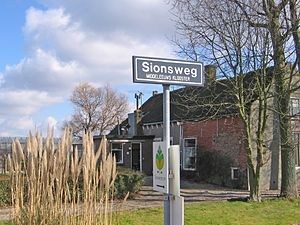 Sion, Netherlands - Road sign in Sion, with the coach house of the former estate in the background.