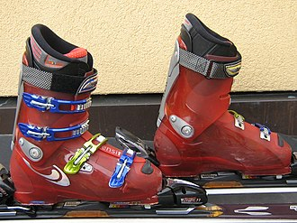 "Ski boot - A pair of modern front-entry alpine ski boots made by Salomon. As with almost all modern examples, four buckles are used to close the openings at the top of the foot and front of the leg to produce stiff cylindrical forms. Above the top buckle on the leg is the ""power strap"", which acts as a fifth buckle. The rivets forming the pivot points that allow the upper and lower portions of the boot to move independently are seen in silver."