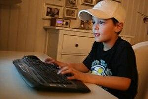 Un garçon devant son ordinateur