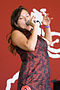 """A colour photo of Tagaq on stage singing. She is holding a microphone while wearing a red and black dress."""