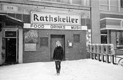 Snowy B&W image of the venue with a woman (Aimee Mann) standing in front