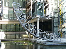 The Rolling Bridge at Paddington is lifted. It is in an unusual curved shape, with one end lifted into the air.