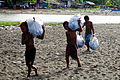 Three young boys carry big bags of rubbish after the clean up day at the Lord Howe settlement, Honiara. (10729887104).jpg
