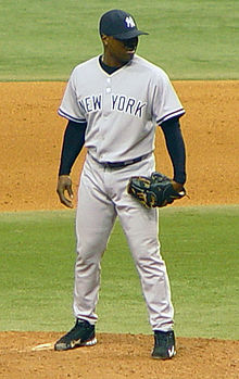 "A dark-skinned man in a gray baseball uniform with ""New York"" across the chest in navy-blue letters and a navy-blue baseball cap standing on a dirt mound on a grass field and wearing a black baseball glove on his left hand"