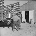 Topaz, Utah. Daily supply of milk being delivered by young evacuee workers at the mess kitchen door. - NARA - 538797.tif