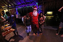 A man dressed as Santa hugging two women in a small night club