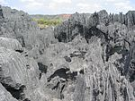 A complex, heavily eroded dark grey limestone rock formation.