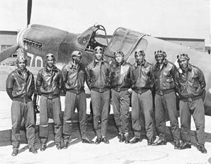 99th Flying Training Squadron - Eight Tuskegee Airmen in front of a  P-40 fighter aircraft
