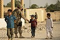 U.S. Air Force Staff Sgt. Michael Sweeney, assigned to the 455th Expeditionary Security Forces Group, exchanges greetings with a boy while providing security in the town of Saka near Bagram Airfield 130613-F-YL744-016.jpg