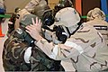 U.S. Air Force Tech. Sgt. Daniel Contino, left, receives help donning his gas mask from Tech. Sgt. David Fickau, both with the 175th Aircraft Maintenance Squadron, during a simulated chemical attack during 140111-Z-PA115-001.jpg