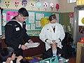 US Navy 030312-N-0000X-001 Dental Technician 3rd Class Omar Pereyra (Left) and Lt. Angela Estepp check a student's teeth during National Children's Dental Health Month.jpg