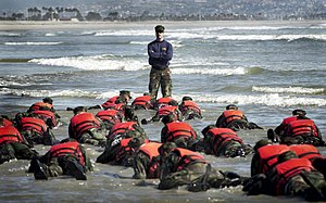 United States Navy SEAL selection and training - Image: US Navy 030415 N 3953L 039 During a Hell Week surf drill evolution, a Navy SEAL instructor assists students from Basic Underwater Demolition SEAL (BUD S) class 245 with learning the importance of listening