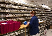 US Navy 030819-N-9593R-078 A Navy hospital corpsman unwraps medication to replenish one of the hundreds of bins in the pharmacy at the National Naval Medical Center in Bethesda, Maryland.jpg