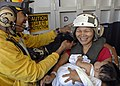 US Navy 070702-N-4954I-028 Aviation Boatswain's Mate Handling 1st Class Lawrence Salalila helps put a cranial on a Filipino mother prior to an airlift from USS Peleliu (LHA 5).jpg