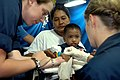 US Navy 070702-N-9421C-002 Ensign Katherine Phillips from the Naval Medical Center, San Diego, prepares to administer an IV to a Filipino child while Hospital Corpsman 3rd Class Barbara Linerooth comforts him before going into.jpg