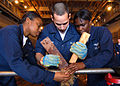 US Navy 090119-N-6282K-218 Storekeeper 3rd Class Darcy Stanford, Ship's Serviceman Seaman Alexander Britt and Airman Jewel Townsend apply a soft patch to a pipe patching simulator during a damage control Olympics.jpg