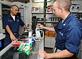 US Navy 090201-N-1082Z-005 Ship's Serviceman 3rd Class Romulo Casavilca monitors a transaction as Fire Controlman 3rd Class Terrence Martinez uses his Navy Cash card in the ship's store.jpg
