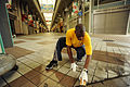 US Navy 100827-N-8335D-037 Legalman 2nd Class Alain Bois, assigned to Fleet Activities Sasebo, cleans the city's main shopping arcade during a community service project.jpg