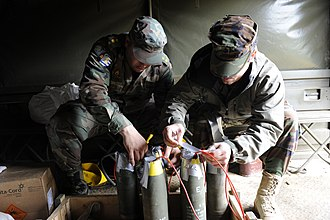 Booby trap - A group of 105mm artillery shells with plastic explosive stuffed into their fuze pockets. Each of the 5 shells has been linked together with red detcord to make them detonate simultaneously. To turn this assembly into a booby trap, the final step would be to connect an M142 firing device to the detcord and hide everything under some form of cover e.g. newspapers or a bed-sheet.
