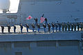 US Navy 110404-N-DM338-403 Sailors aboard JDS Hyuga (DDH 181) wave the American and Japanese flags as a sign of friendship during a pass and review.jpg