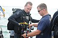 US Navy 110707-N-MN220-074 Navy Diver 2nd Class Nick Barna, left, a basic diver assigned to Navy Dive Locker Guantanamo, receives a pre-dive equipm.jpg