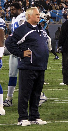 Candid photograph of Phillips standing with arms akimbo on a football field wearing a dark blue jacket with a Dallas Cowboys logo