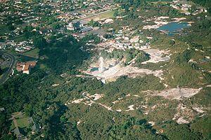Whakarewarewa - Aerial view of Whakarewarewa; Pohutu Geyser is erupting