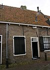foto van Eenvoudig woonhuis in gele baksteen onder een gezamenlijk met de nrs 4,8 en 10 dwars, met pannen belegd zadeldak, vlakgemetselde ontlastende korfbogen boven de vensters